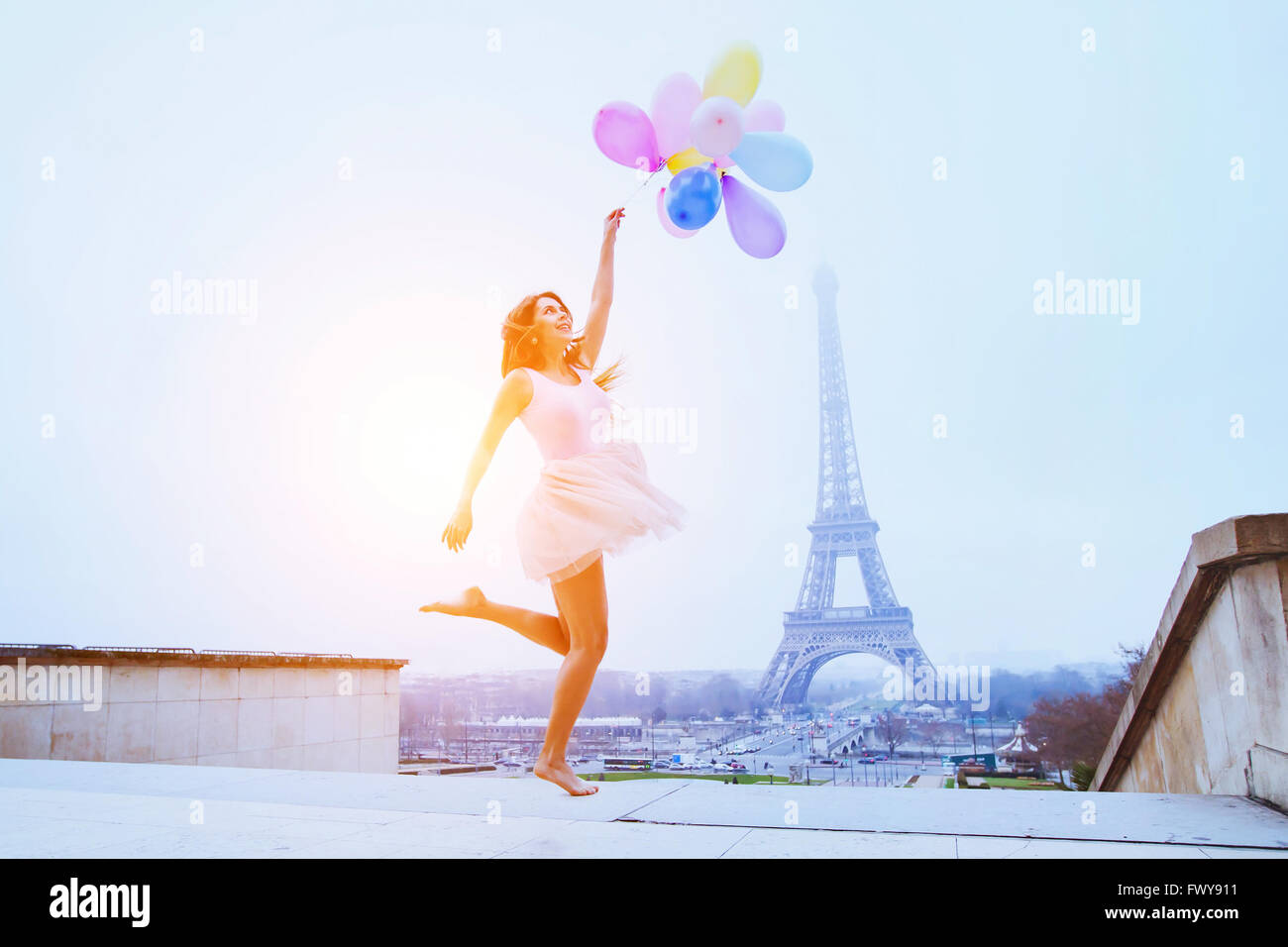 dream travel, girl with balloons jumping near Eiffel Tower in Paris - Stock Image
