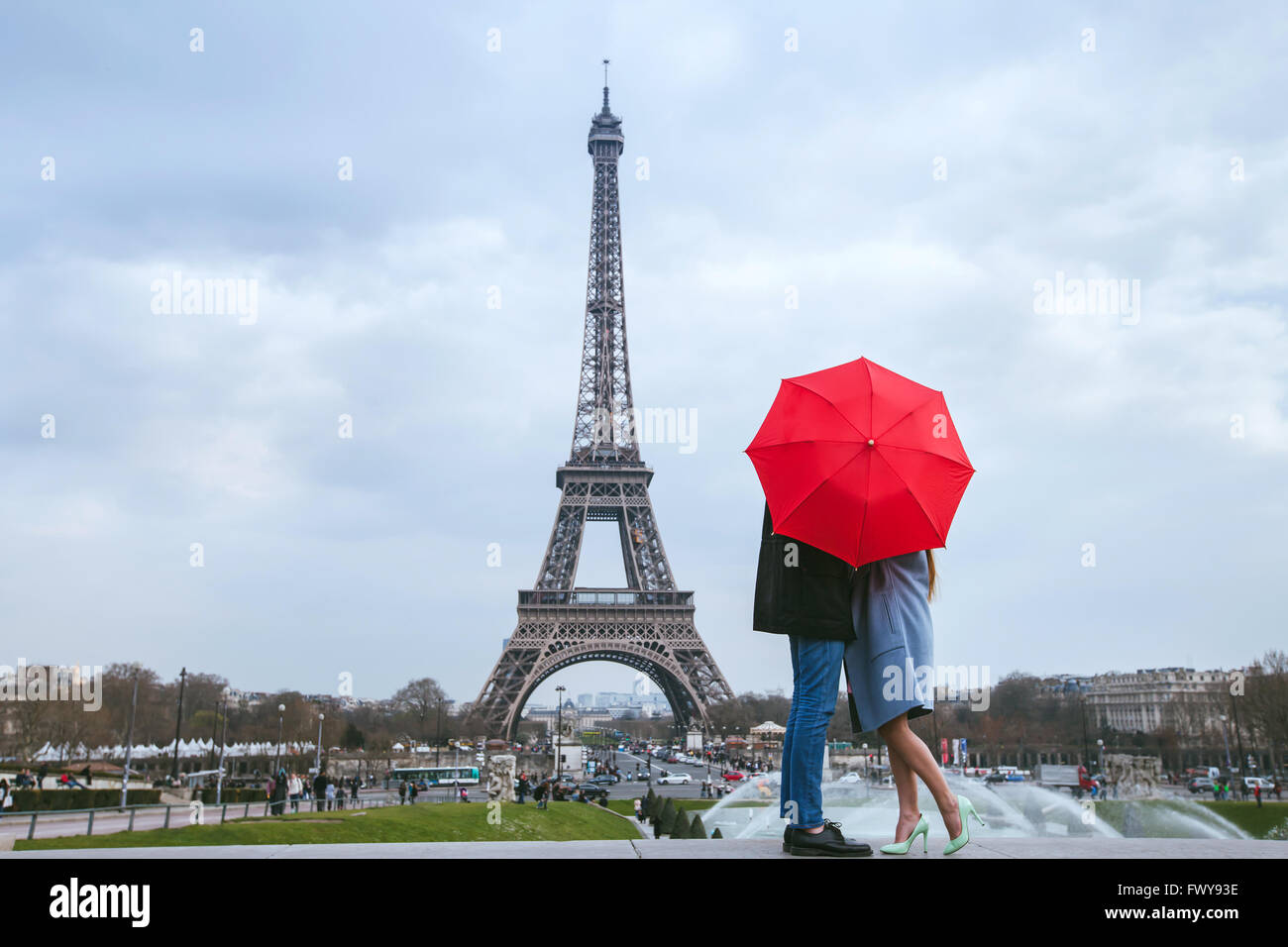 honeymoon in Paris, couple kissing behind red umbrella against Eiffel tower - Stock Image