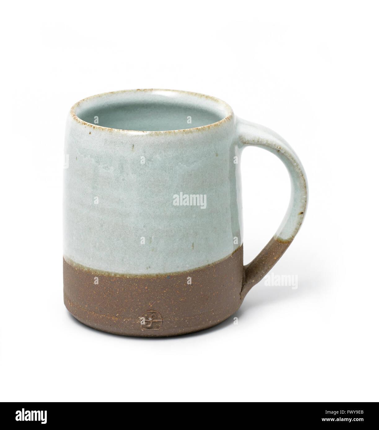 Earthenware grey brown mug white background - Stock Image