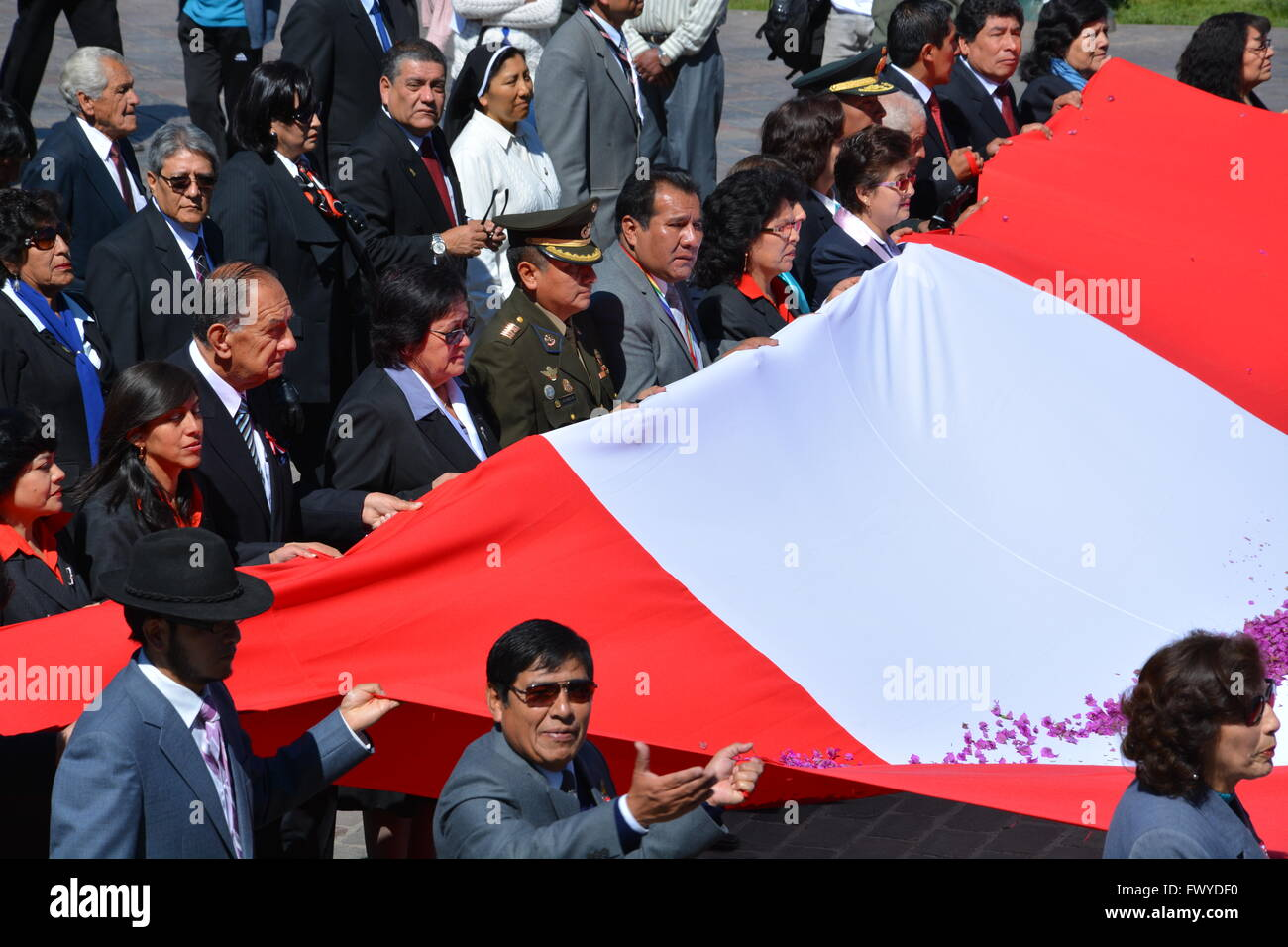 Politicians and dignitaries carry the Peruvian flag and parade around the Plaza de Armas for Dia del Folclor in - Stock Image