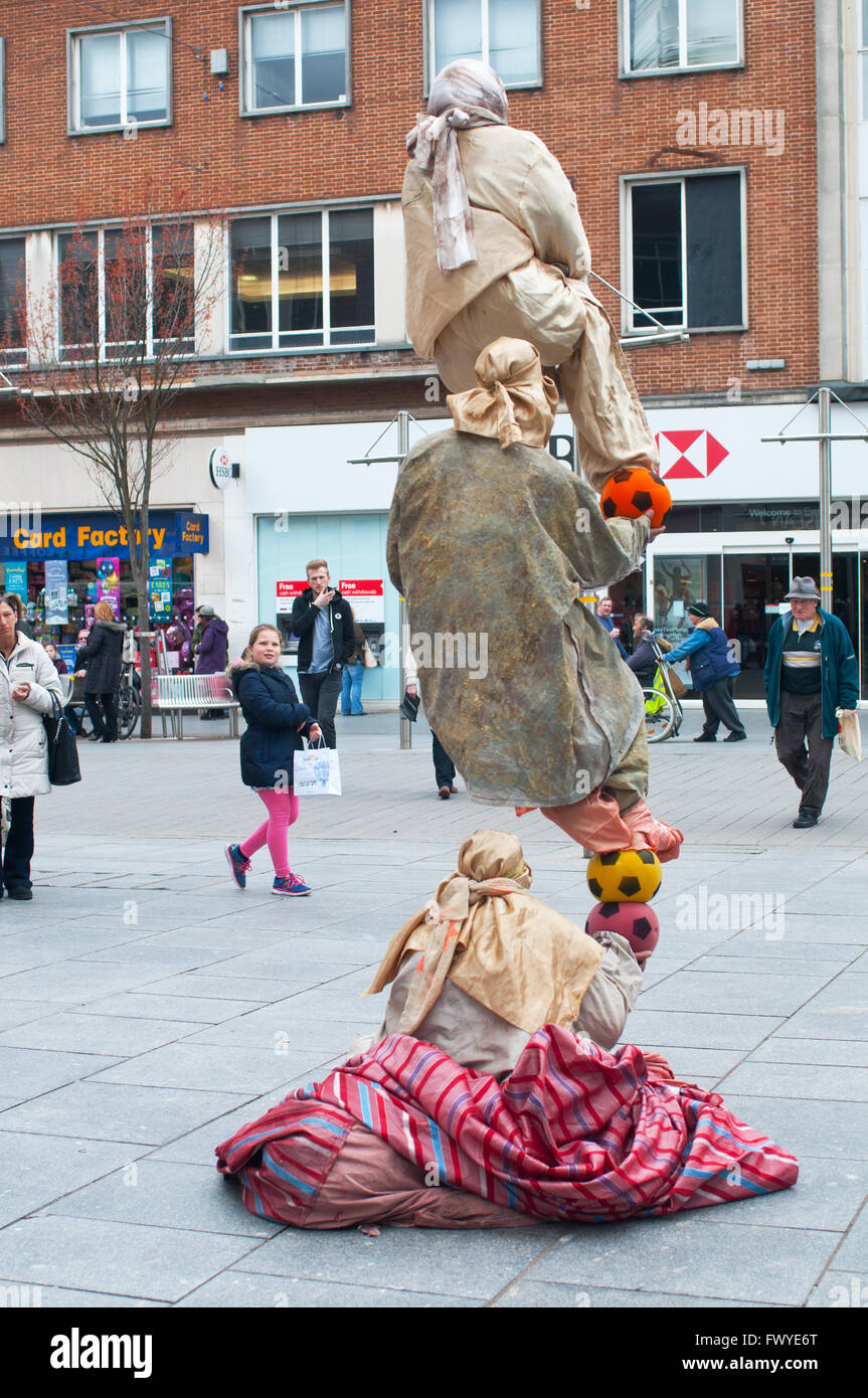 Street entertainers performing a balancing act. - Stock Image