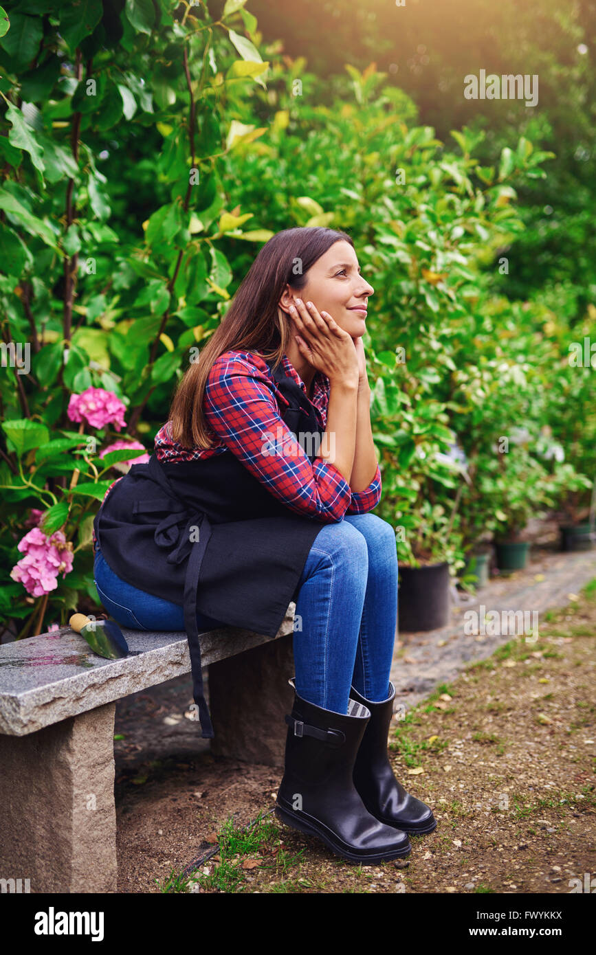 Pretty young nursery worker sitting on a wooden bench daydreaming with a smile of pleasure on her face as she takes - Stock Image