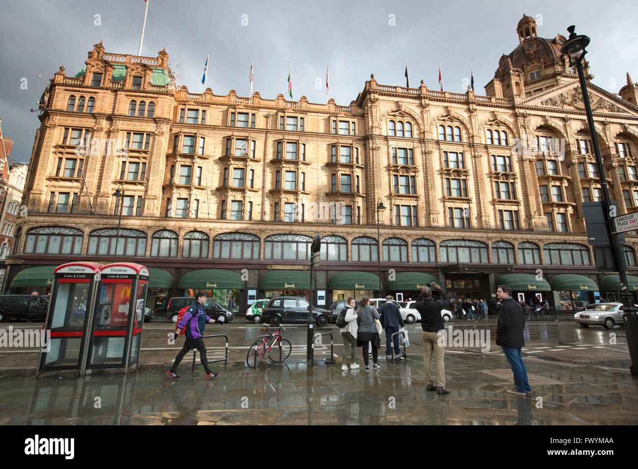 Exterior of Harrods luxury department store on a gray stormy day, Brompton Road, London, England, UK - Stock Image
