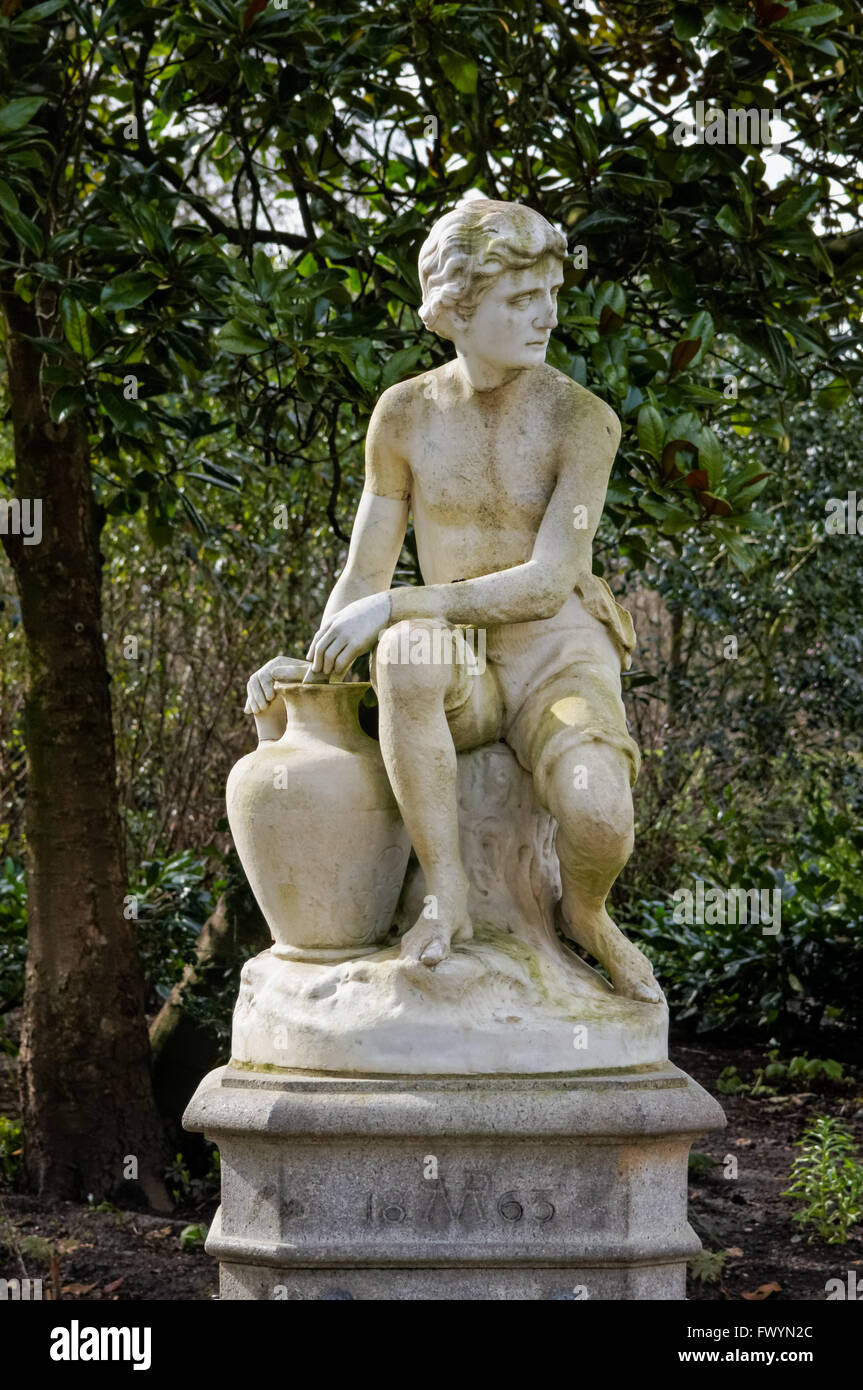 A drinking fountain statue of a seated boy in St James's Park, London England United Kingdom UK - Stock Image