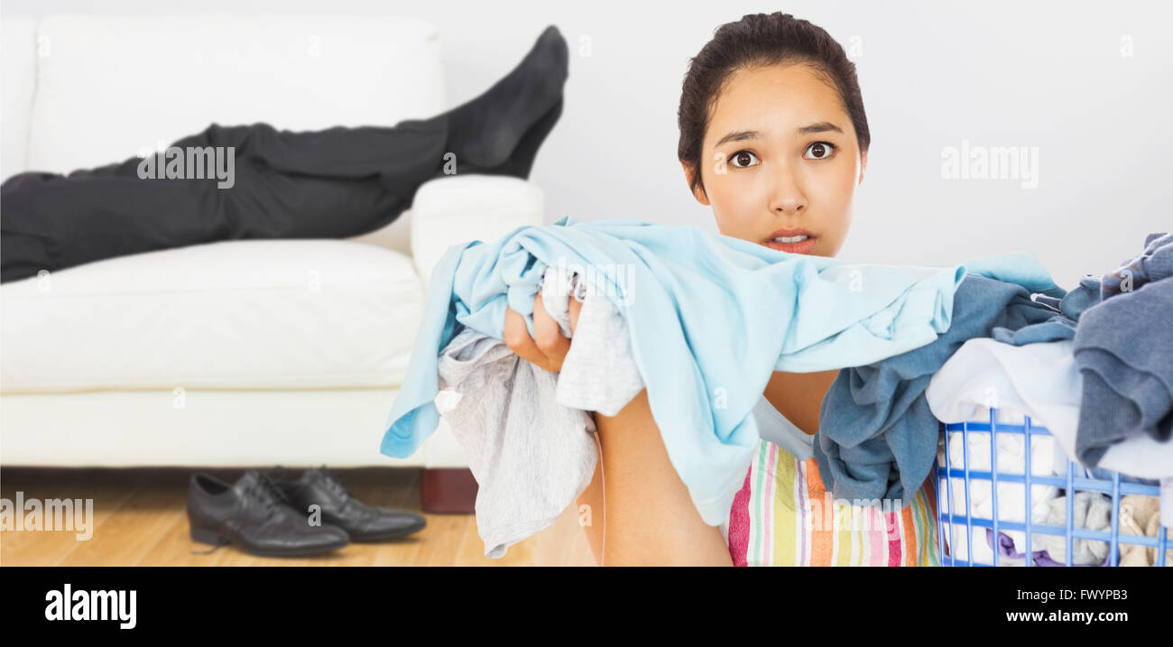 Composite image of frowning woman taking out dirty laundry - Stock Image