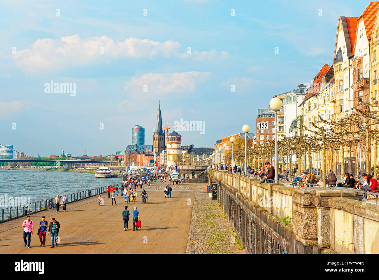 DUSSELDORF, GERMANY - MAY 3, 2013: Dusseldorf Rhine Embankmentr with tourists and St Lambertus Collegiate Church and Schiffahrtmuseum in the background. Stock Photo