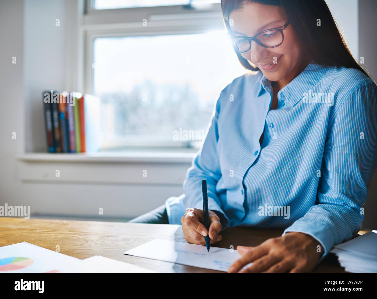 Selective focus close up on happy entrepreneur female wearing glasses and blue shirt at desk writing on form next Stock Photo
