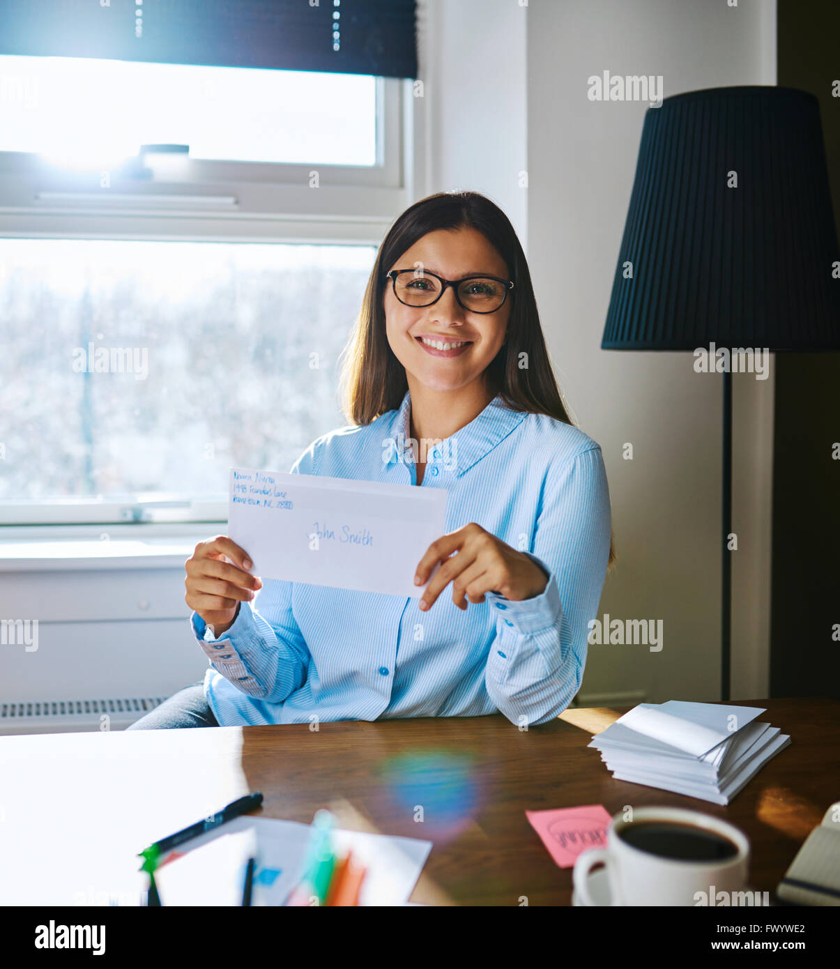 Happy single woman in glasses and light blue blouse holding envelope with handwritten address while seated behind - Stock Image