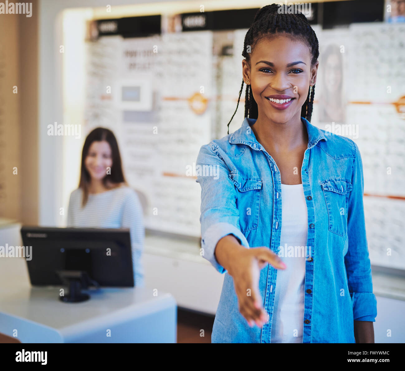 Pretty young African American optometrist greeting a customer at the door with a beaming smile and outstretched - Stock Image
