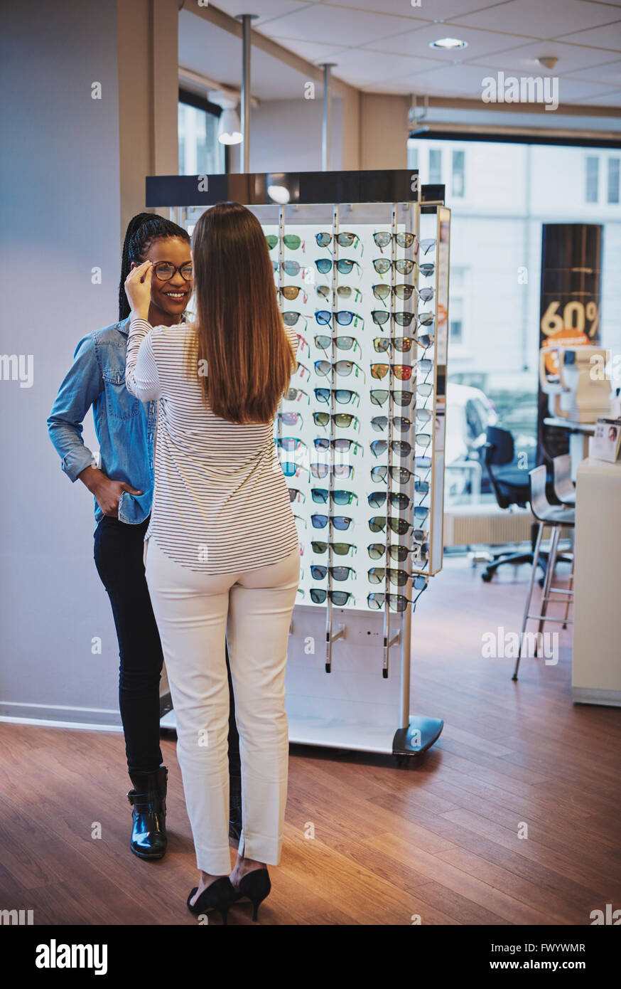 Optometrist fitting glasses for a smiling young African American customer inside the store as she chooses her frames - Stock Image