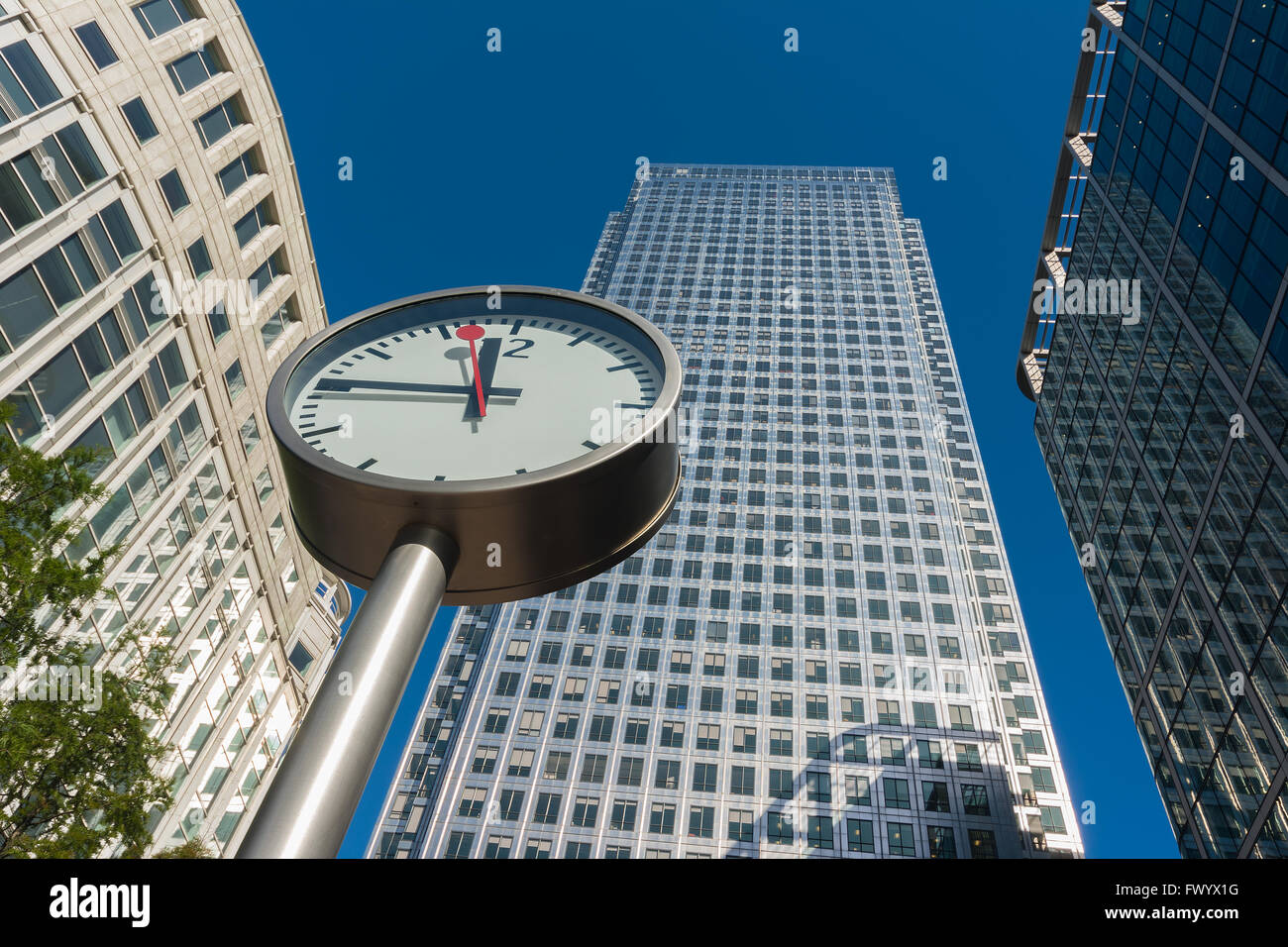 Clock and skyscrapers at Canary Wharf, Docklands the heart of the financial district of London - Stock Image