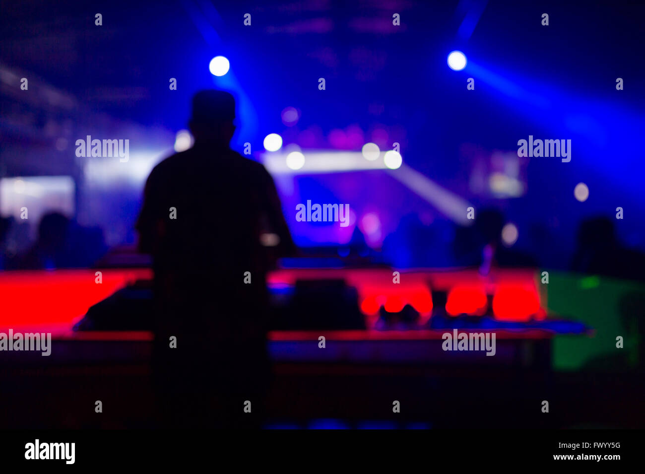 Blurred background : Club, disco DJ playing and mixing music for crowd of happy people. Nightlife, concert lights, - Stock Image