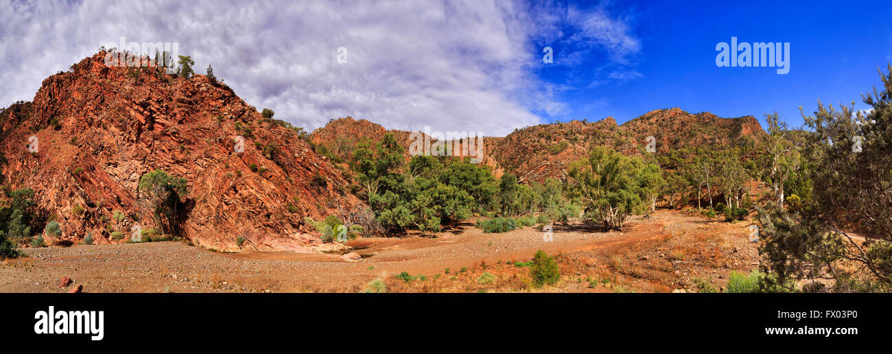 Dry riverbed between ancient limestone rocks in Brachina Gorge of Flinders Ranges national park under blue sky. - Stock Image