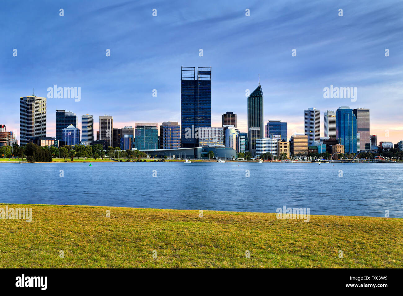 Green grass accross from Perth city CBD over Swan River in Western Australia at sunrise. - Stock Image