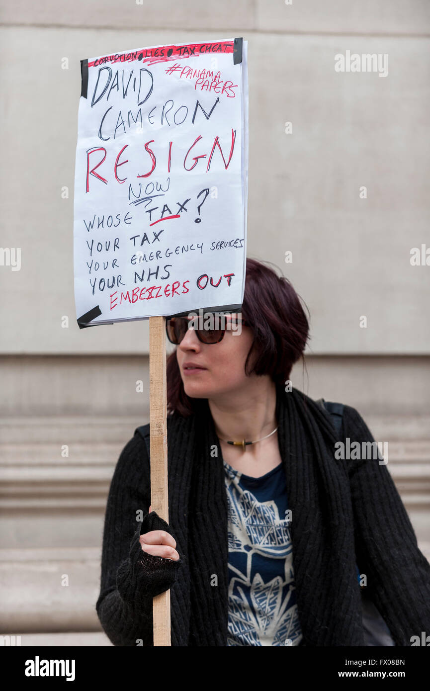 """London, UK. 9 April 2016.  A woman holds a placard aloft outside the Spring Conference.  Thousands of protestors call for the Prime Minister, David Cameron, to resign following his recent comments regarding offshore tax and his father being named in the """"Panama Papers"""" leaks.  Protestors convened outside Downing Street before marching to The Grand Connaught Rooms in Covent Garden where the Conservative Spring Conference is taking place. Credit:  Stephen Chung / Alamy Live News Stock Photo"""