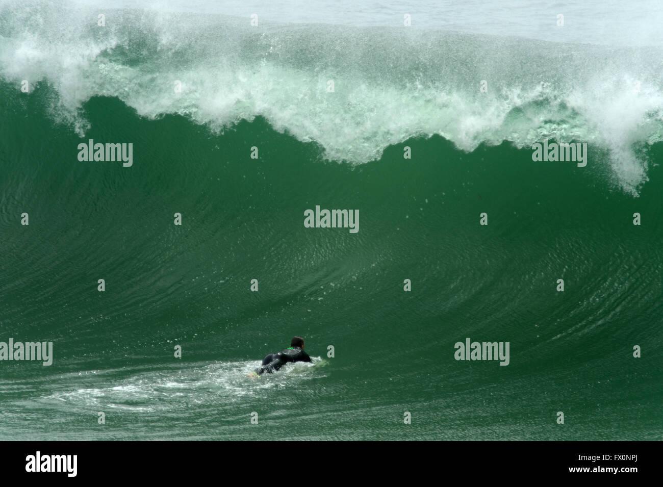 Surfer prepares to duck dive a large wave in the Algarve, Praia do Zavial - Stock Image
