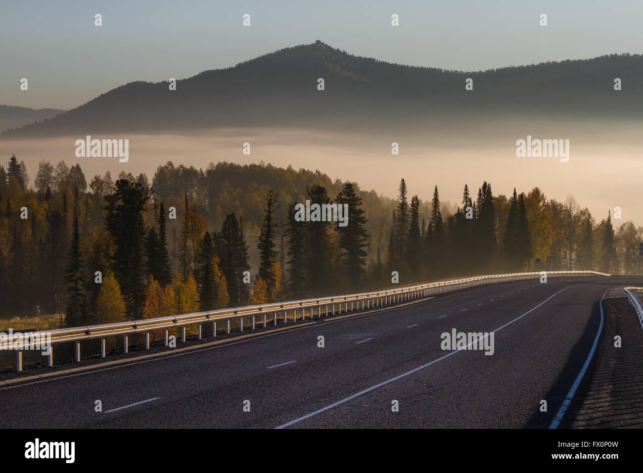 Mountain road at dawn, fog and peaks  in background in Sheregesh, Siberia, Russia - Stock Image
