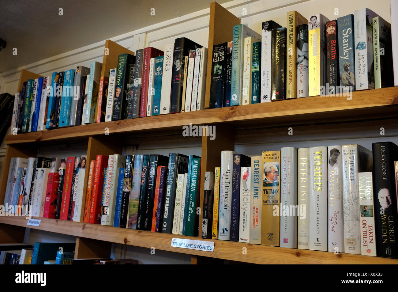 rows of secondhand fiction and non fiction books on wooden shelves in east kent uk april 2016 - Stock Image