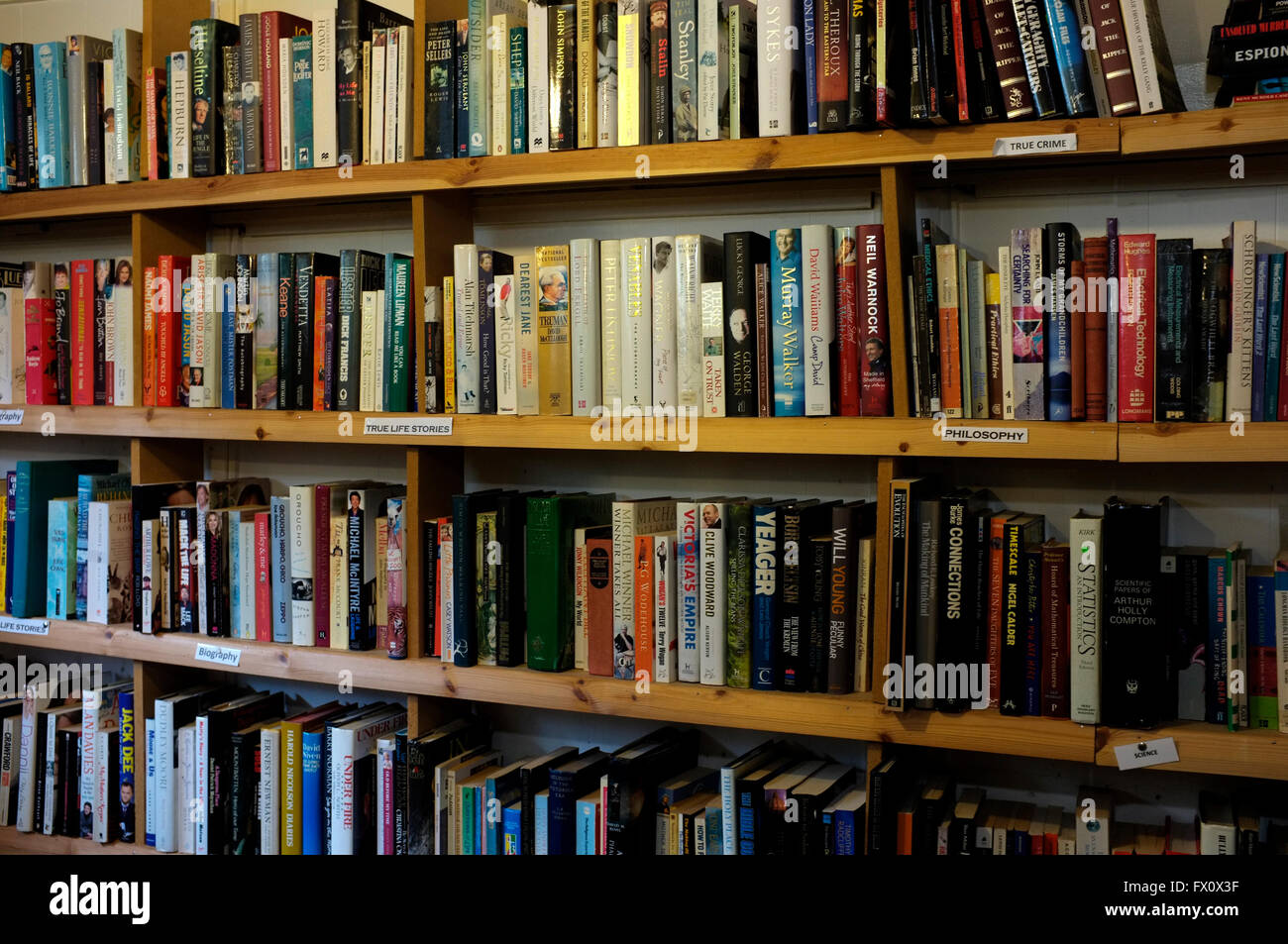 rows of secondhand fiction and non fiction books on wooden shelves in east kent uk april 2016 Stock Photo