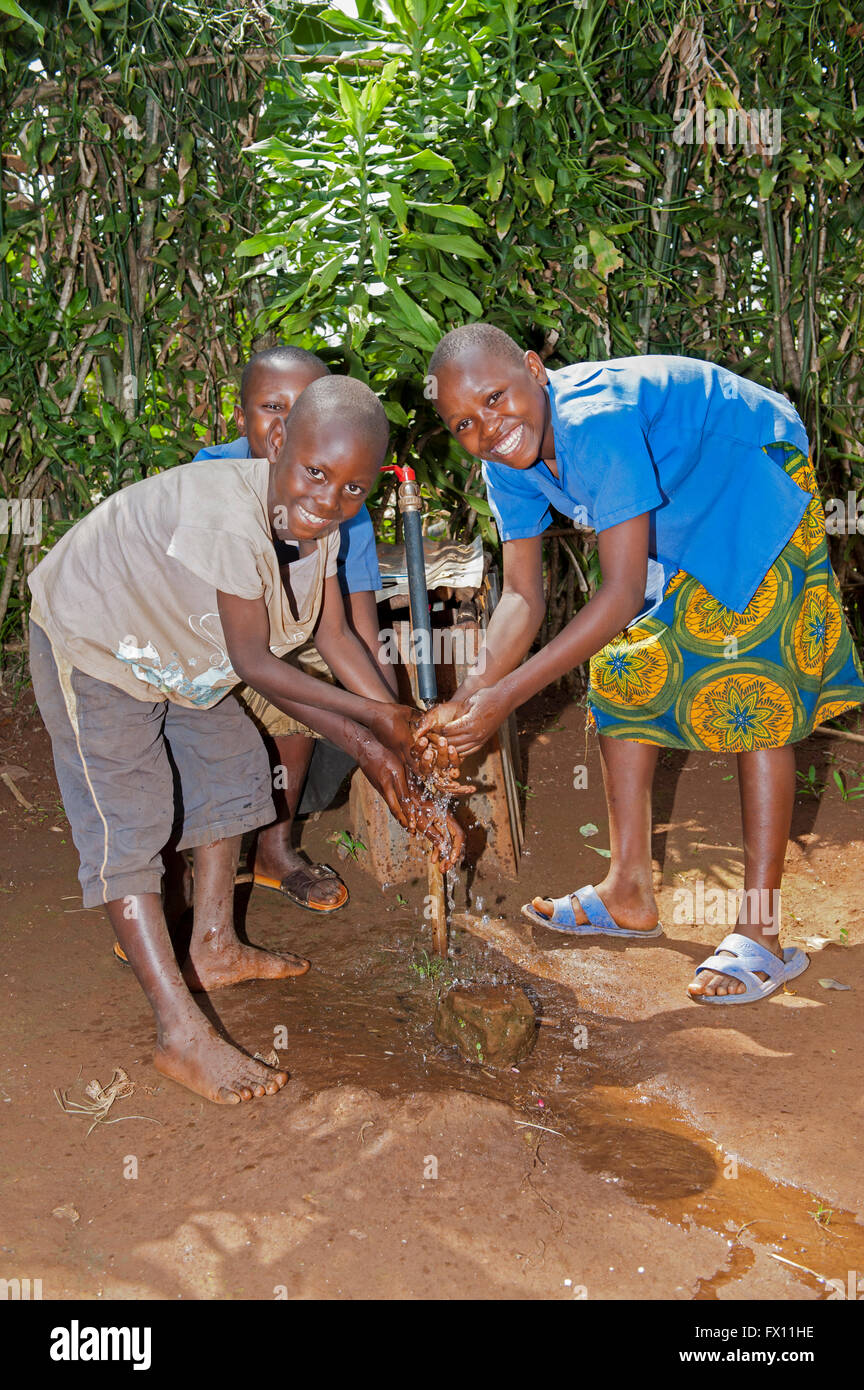 Children washing their hands in fresh, clean water from a well, Rwanda. - Stock Image