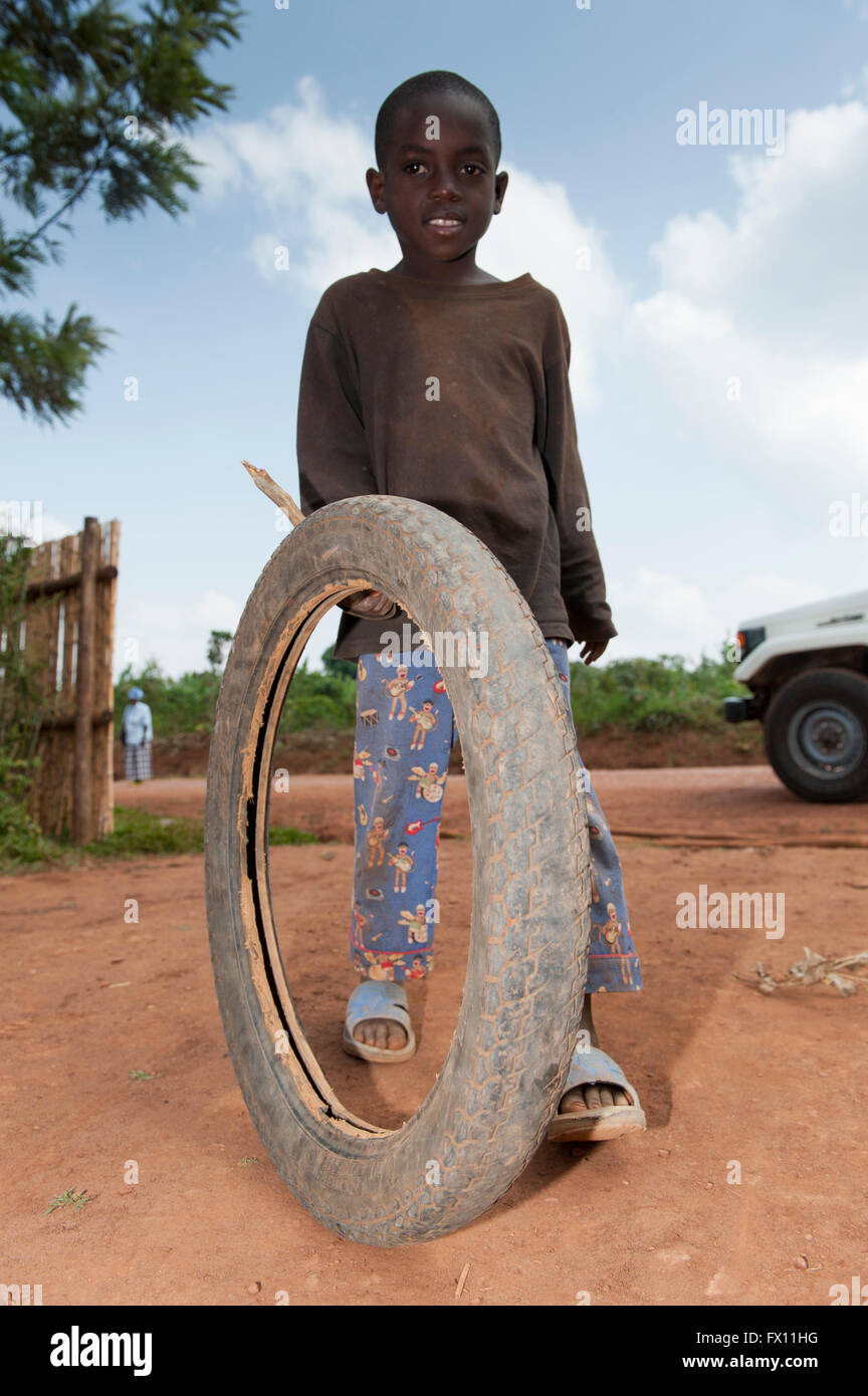 Children playing with a motorcycle tyre and a stick as a toy. Rwanda. - Stock Image