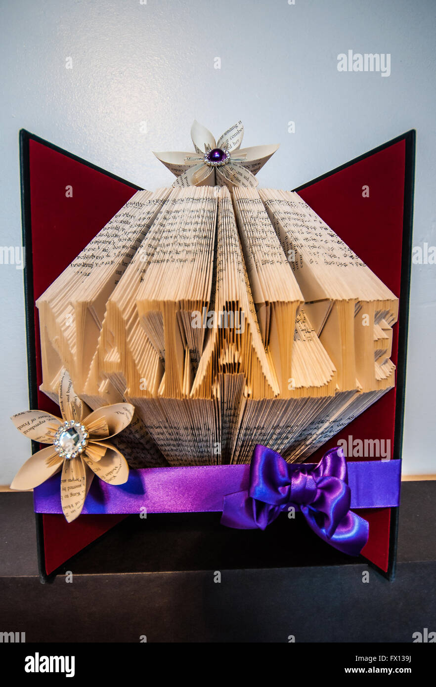 Book Folding. Art created by folding the pages of a hardback book to form images or words. They can be decorated Stock Photo