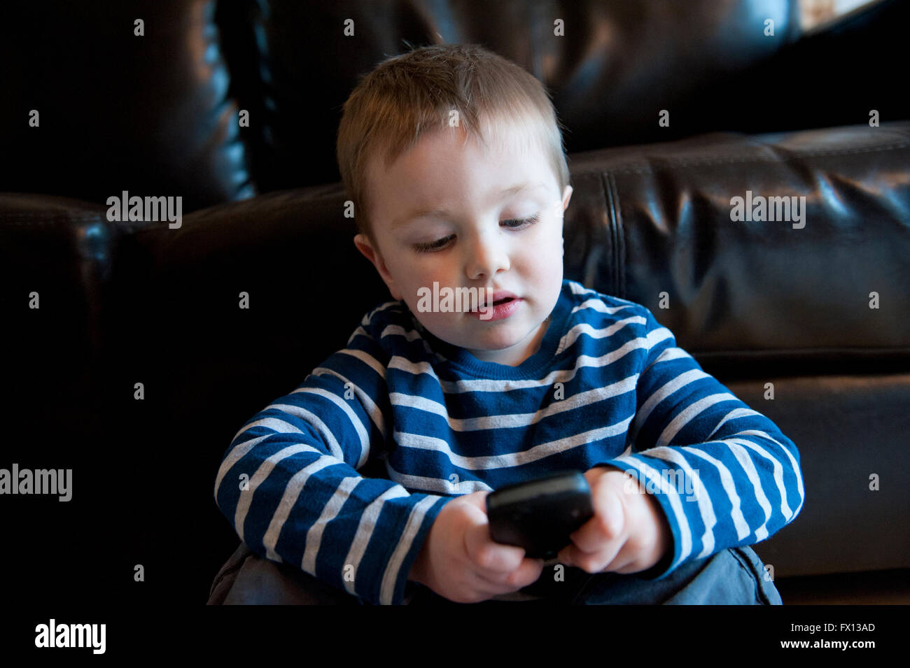 A cute little boy sitting against a brown leather sofa playing a game on a cellphone - Stock Image