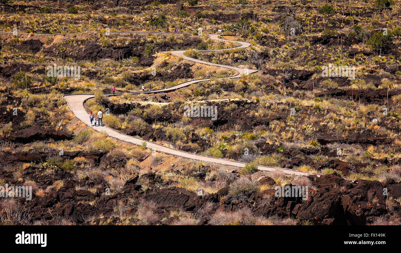 Visitors on the curved walkway through lava fields at Valley of Fires Recreation Area in New Mexico - Stock Image