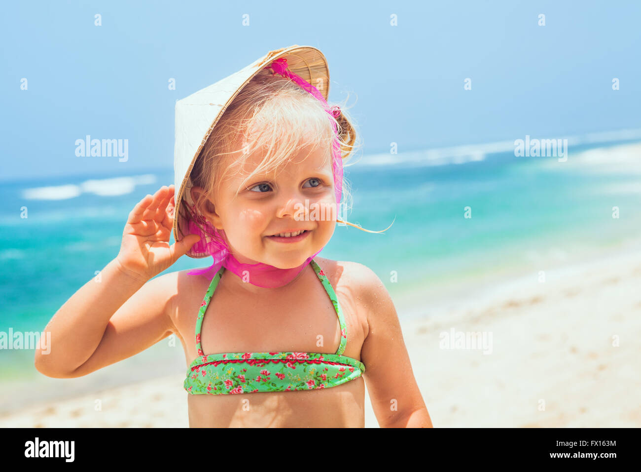 Portrait of beautiful little traveler on sunny white sand beach - happy smiling baby girl in vietnamese straw hat - Stock Image