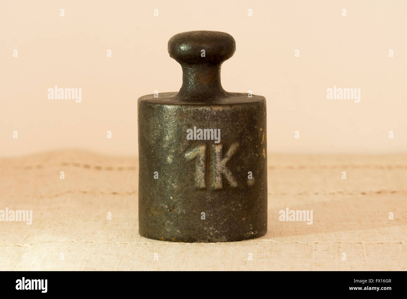 An antique one kilogram weight for use with a weighing scale - Stock Image