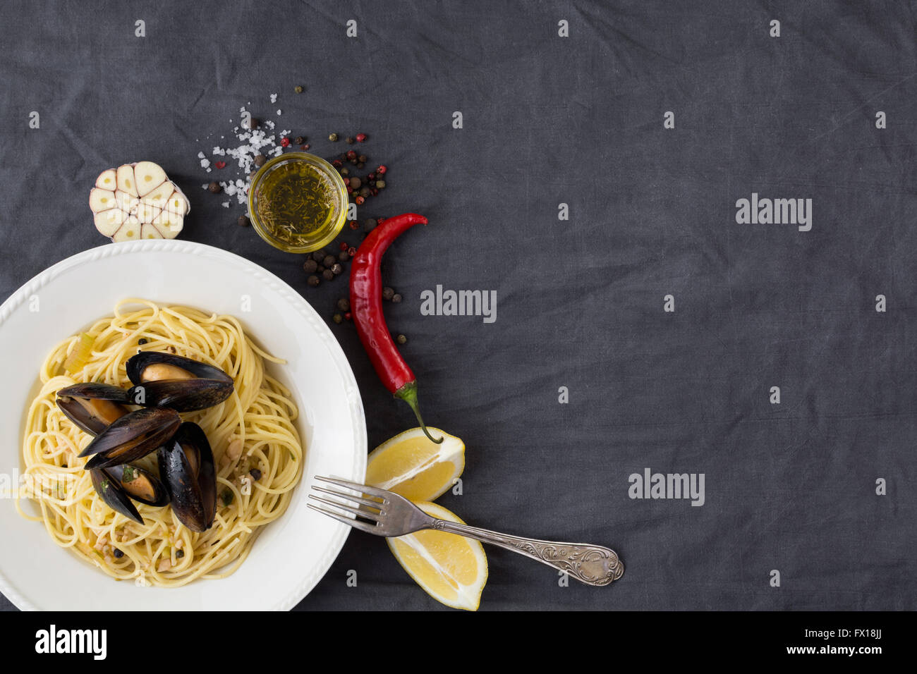 Pasta with mussels, lemons, chili pepper and spices - Stock Image
