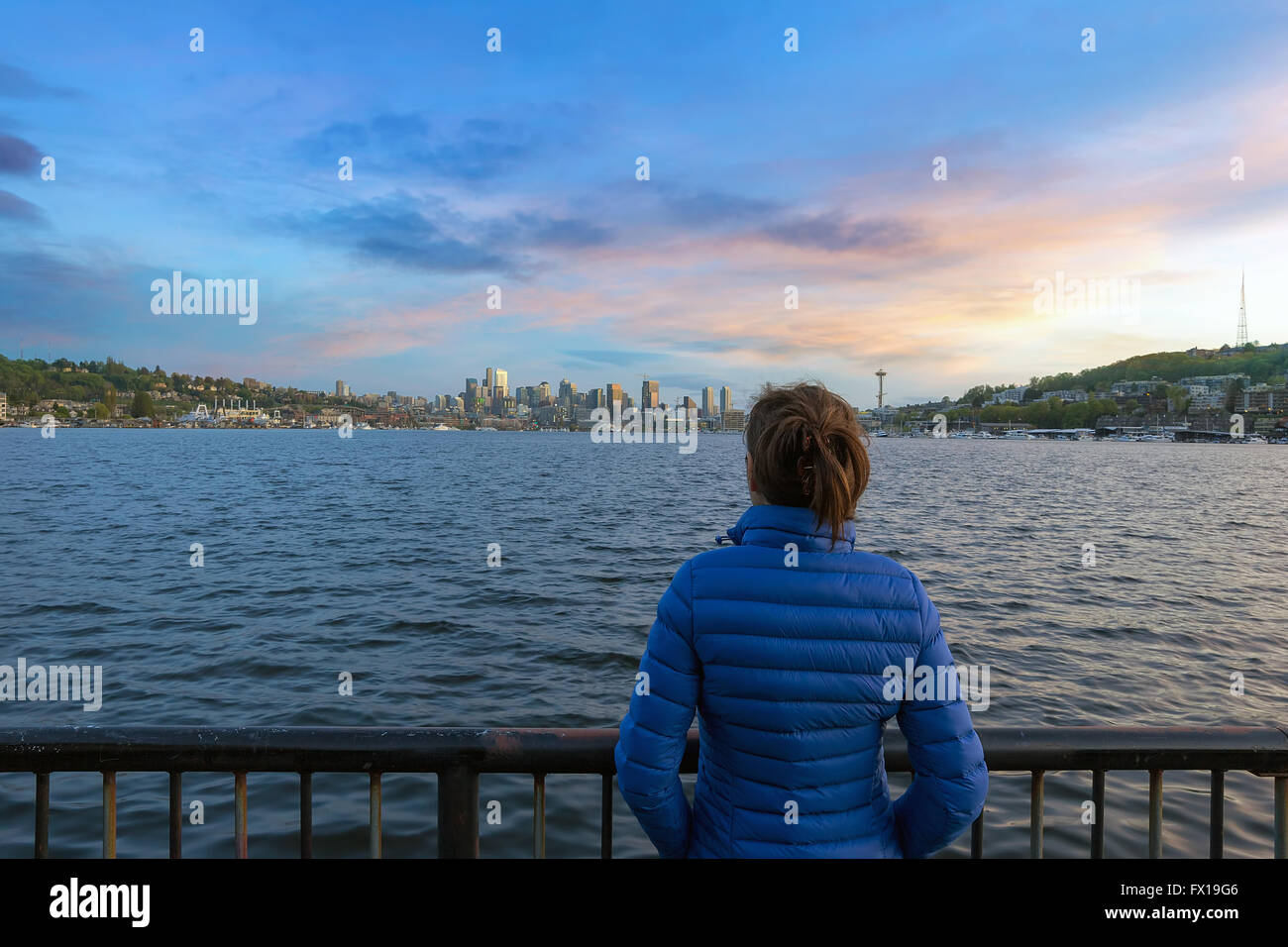 Woman watching sunset over Seattle Washington Skyline along Lake Union from Gas Works Park - Stock Image