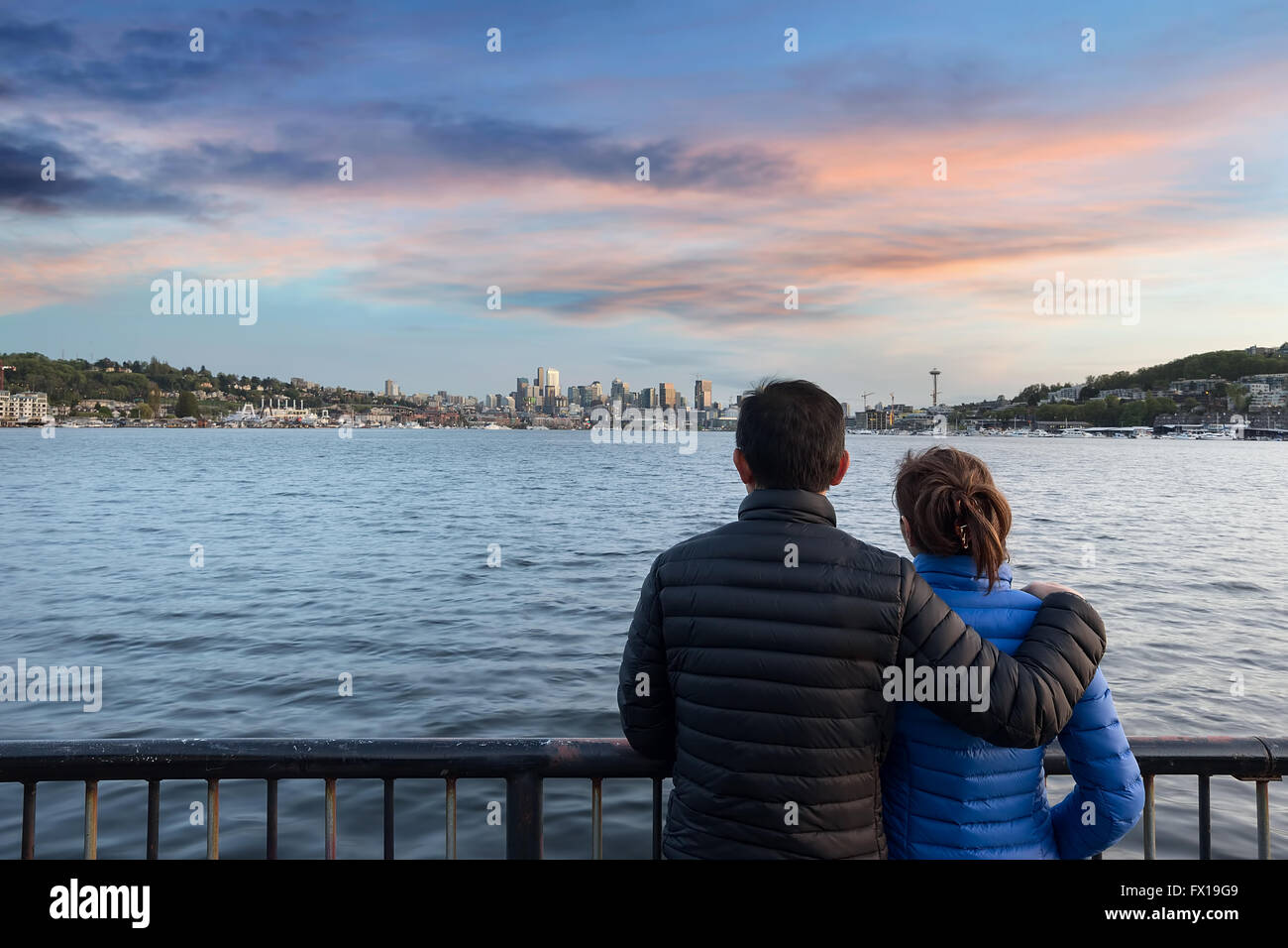 Couple watching sunset over Seattle Washington city skyline along Lake Union - Stock Image