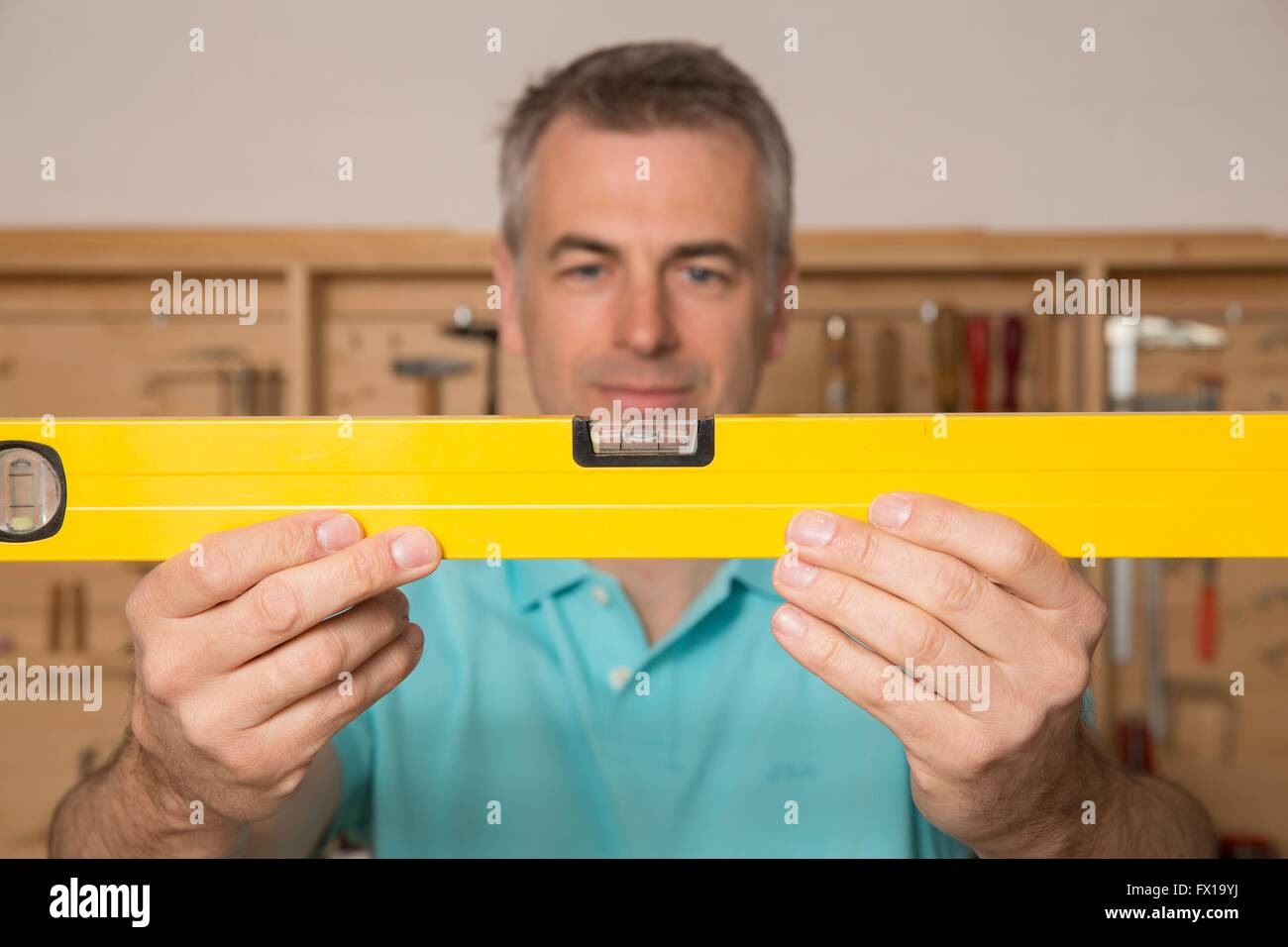 Do-it-yourselfer with a spirit level, portrait - Stock Image
