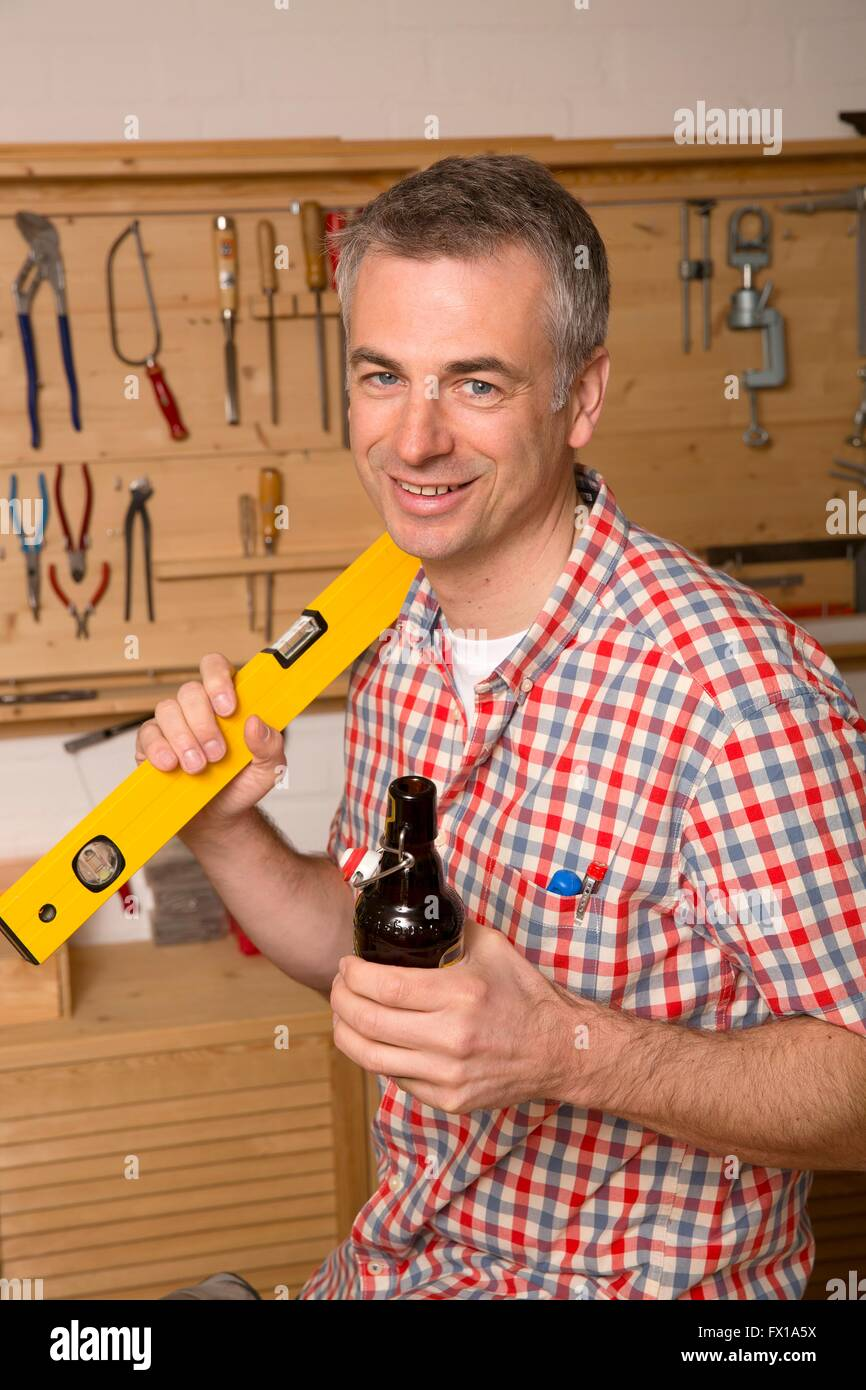 Do-it-yourselfer makes a break and drinks a beer - Stock Image
