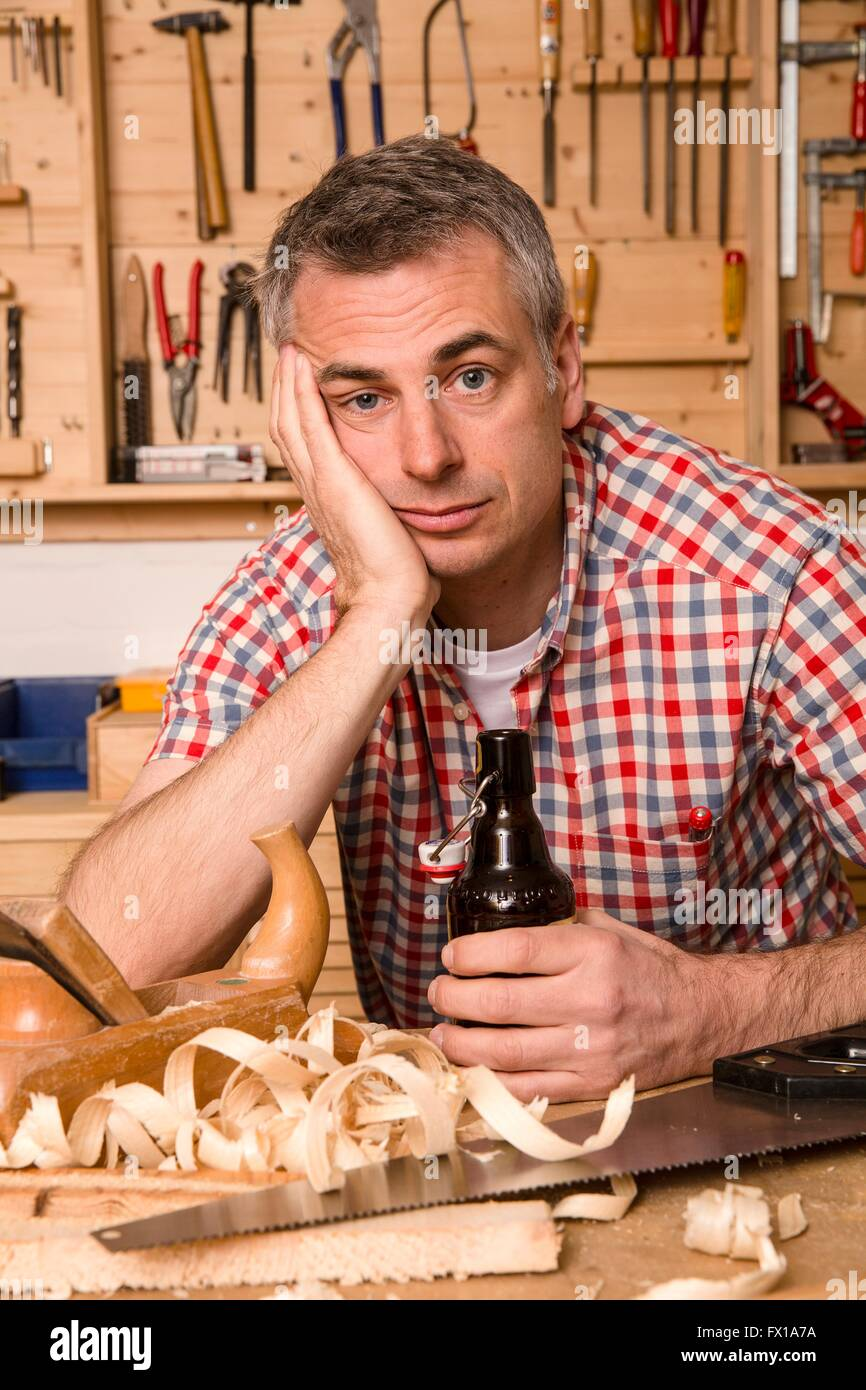 Pensive do-it-yourselfer with a bottle of beer - Stock Image