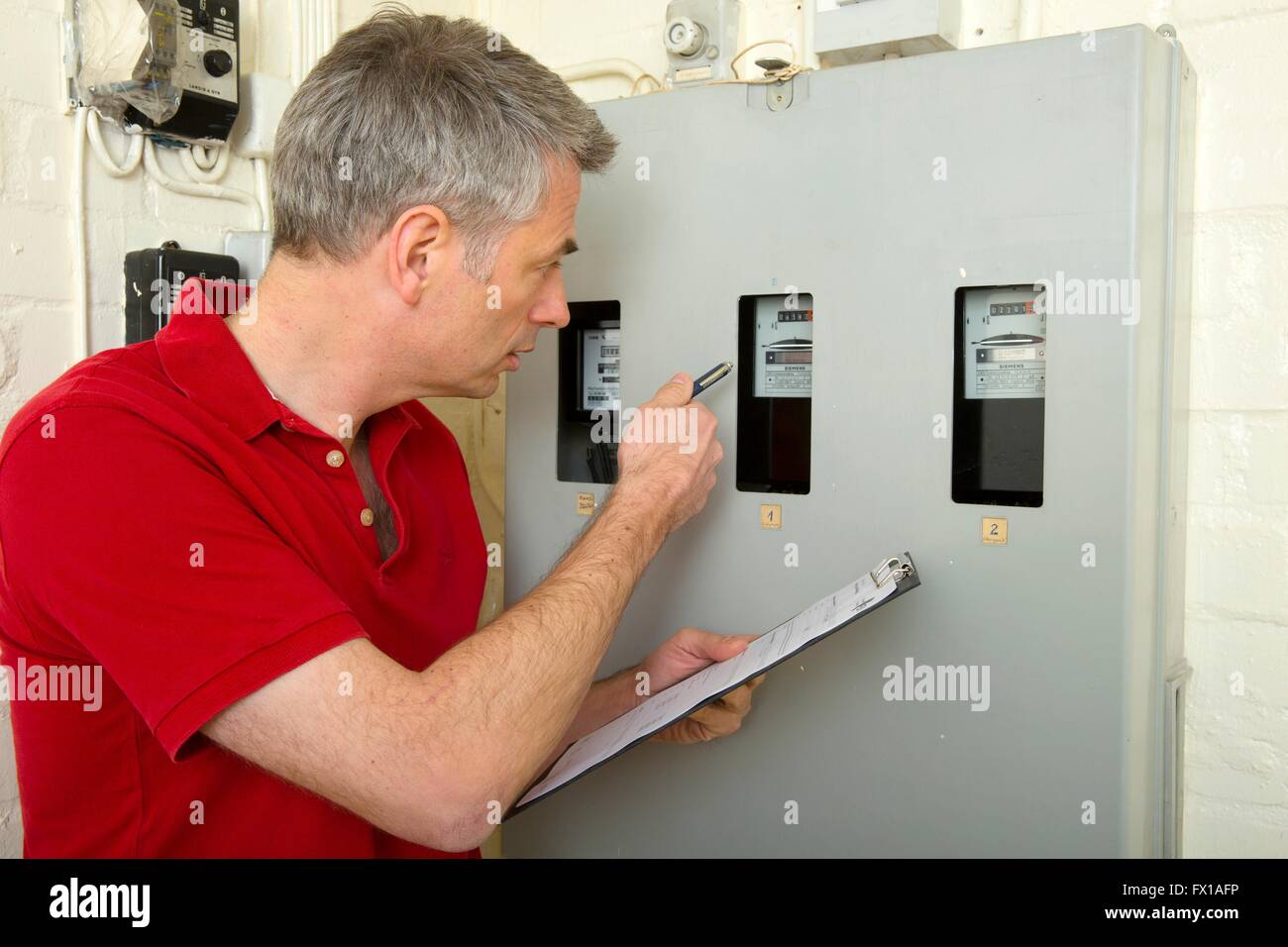 Man reads the power consumption - Stock Image