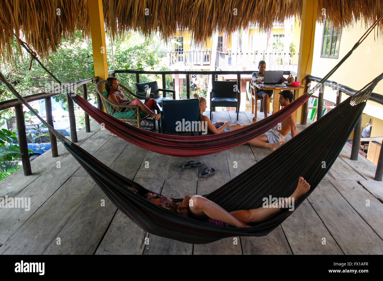 Group of European tourists resting on hammocks. Photographed at El Tunco beach, El Salvador, - Stock Image