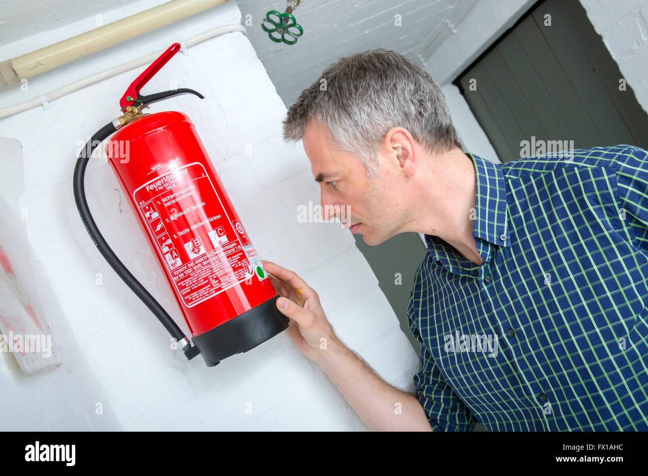 Man controls the fire extinguisher - Stock Image