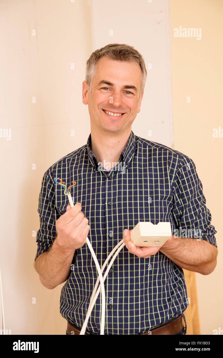 Man with outlet and cable - Stock Image