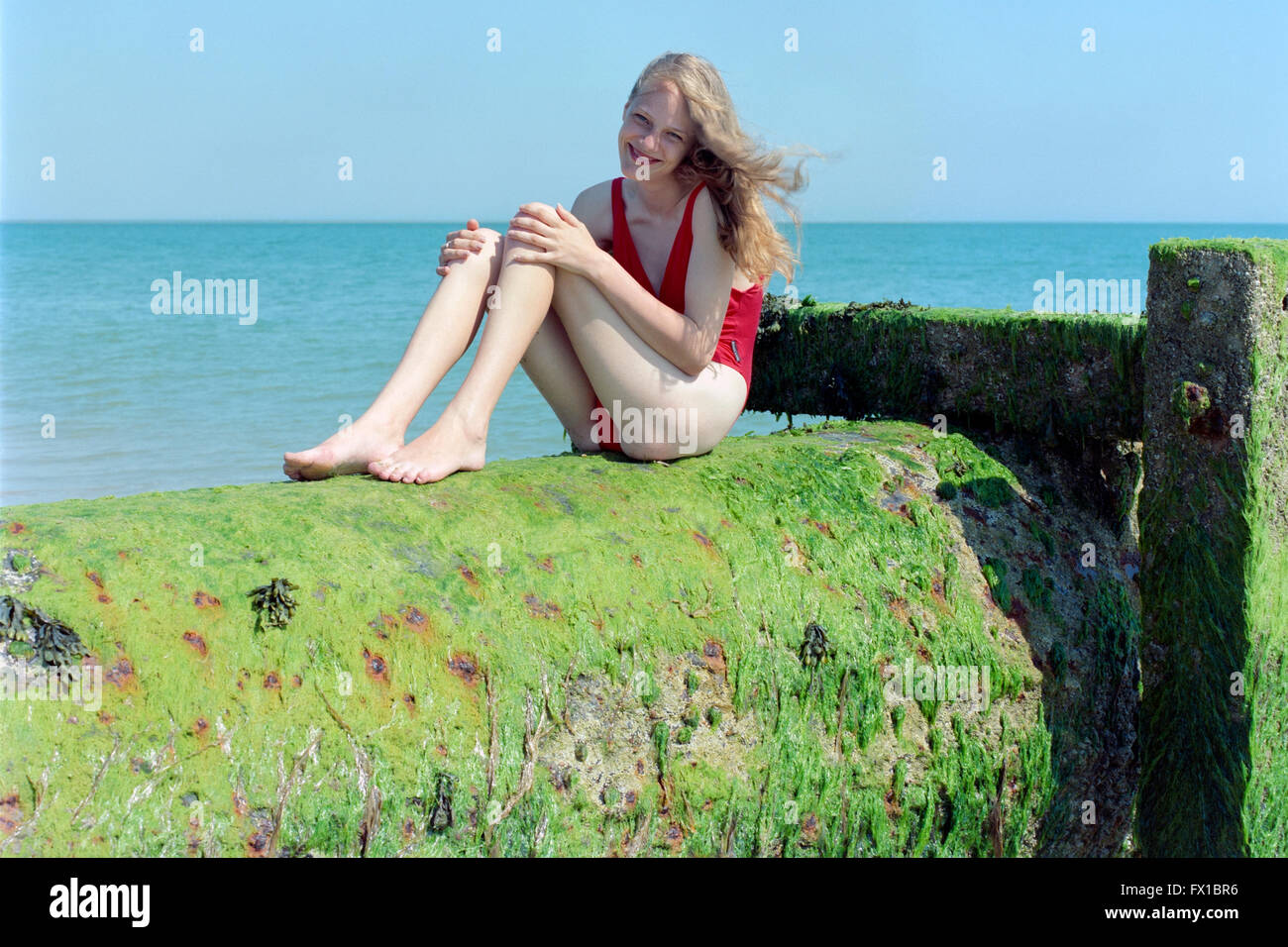young blonde haired female in red swim suit enjoying southsea seafront england uk Stock Photo