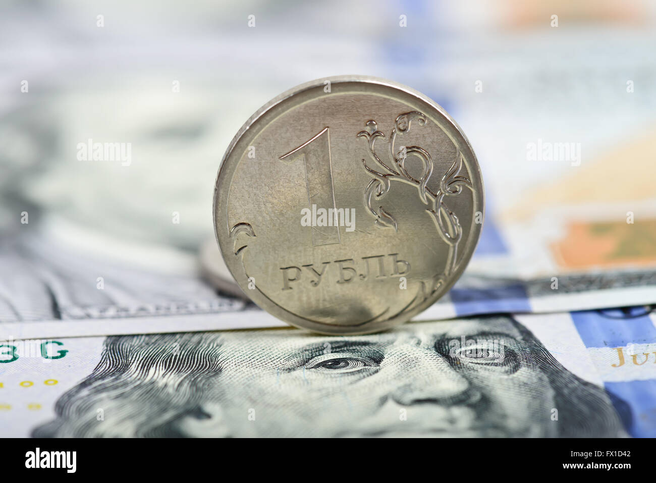 coin one ruble against the background US dollars - Stock Image