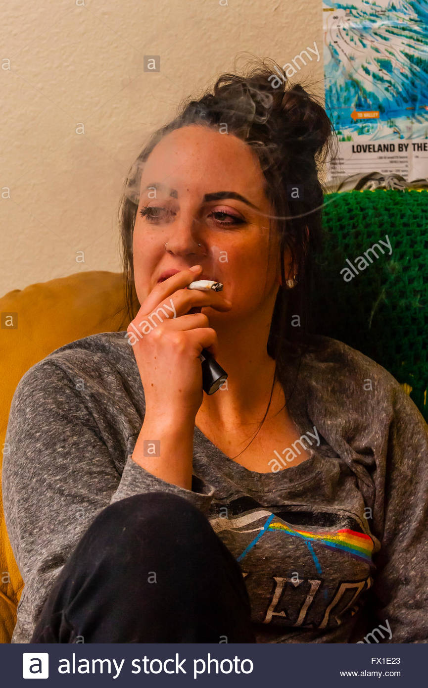 Young people smoking marijuana and relaxing at home, Aurora, Colorado USA.  Colorado was the first state to legalize - Stock Image