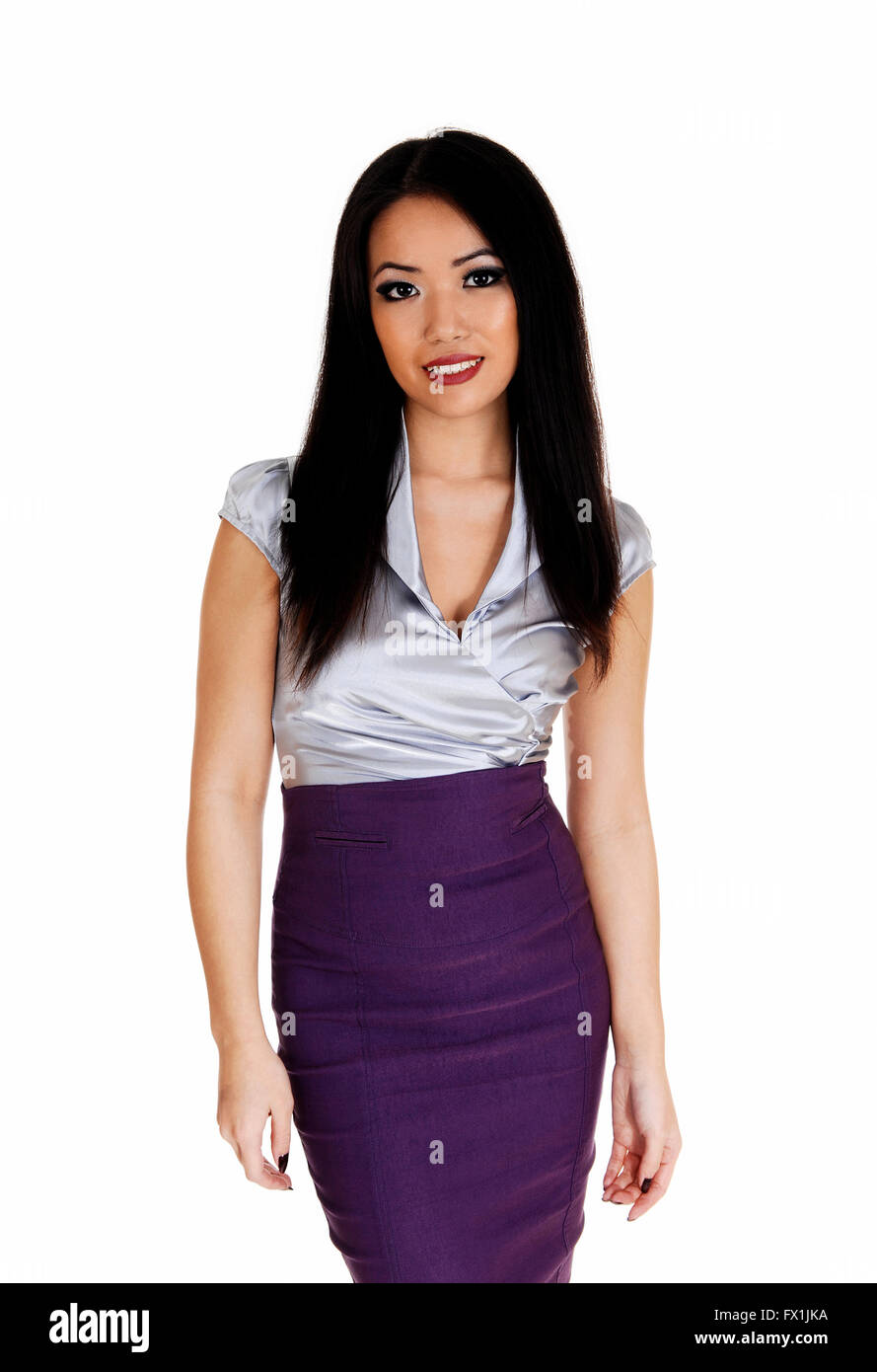 93c06634cd7987 A beautiful young slim Asian business woman in a silver blouse and lilac  skirt with long black hair standing for white backgroun