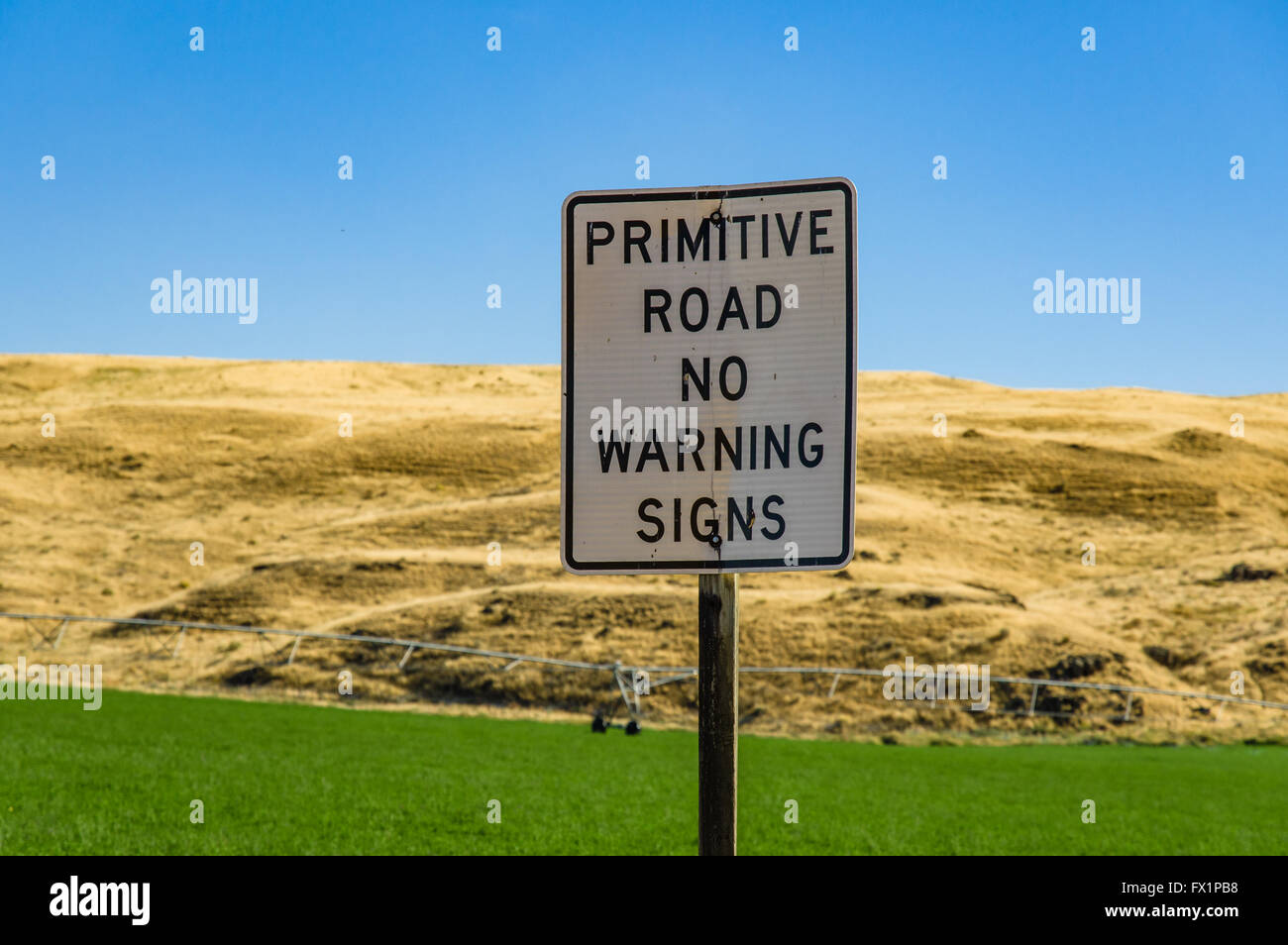 Road sign in rural eastern Washington warning of primitive road conditions - Stock Image
