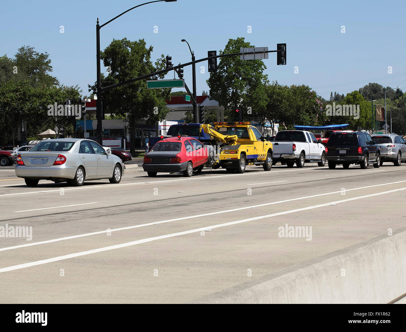 Yellow Tow Truck Hauling Car In Traffic - Stock Image
