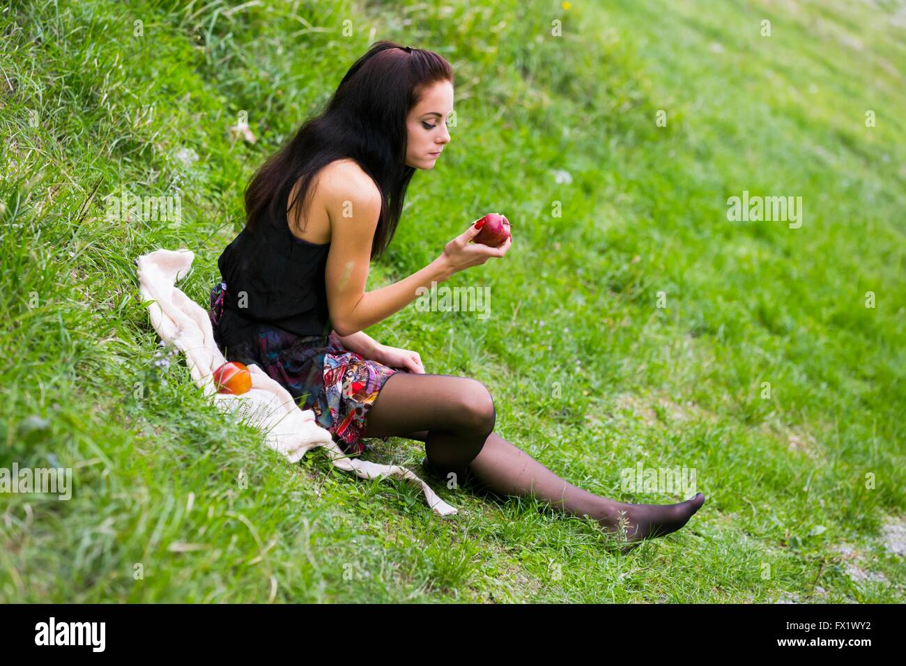 Teen girl with apple in hand on greenfield sitting angled barefeet outdoors attractive lifestyle Stock Photo