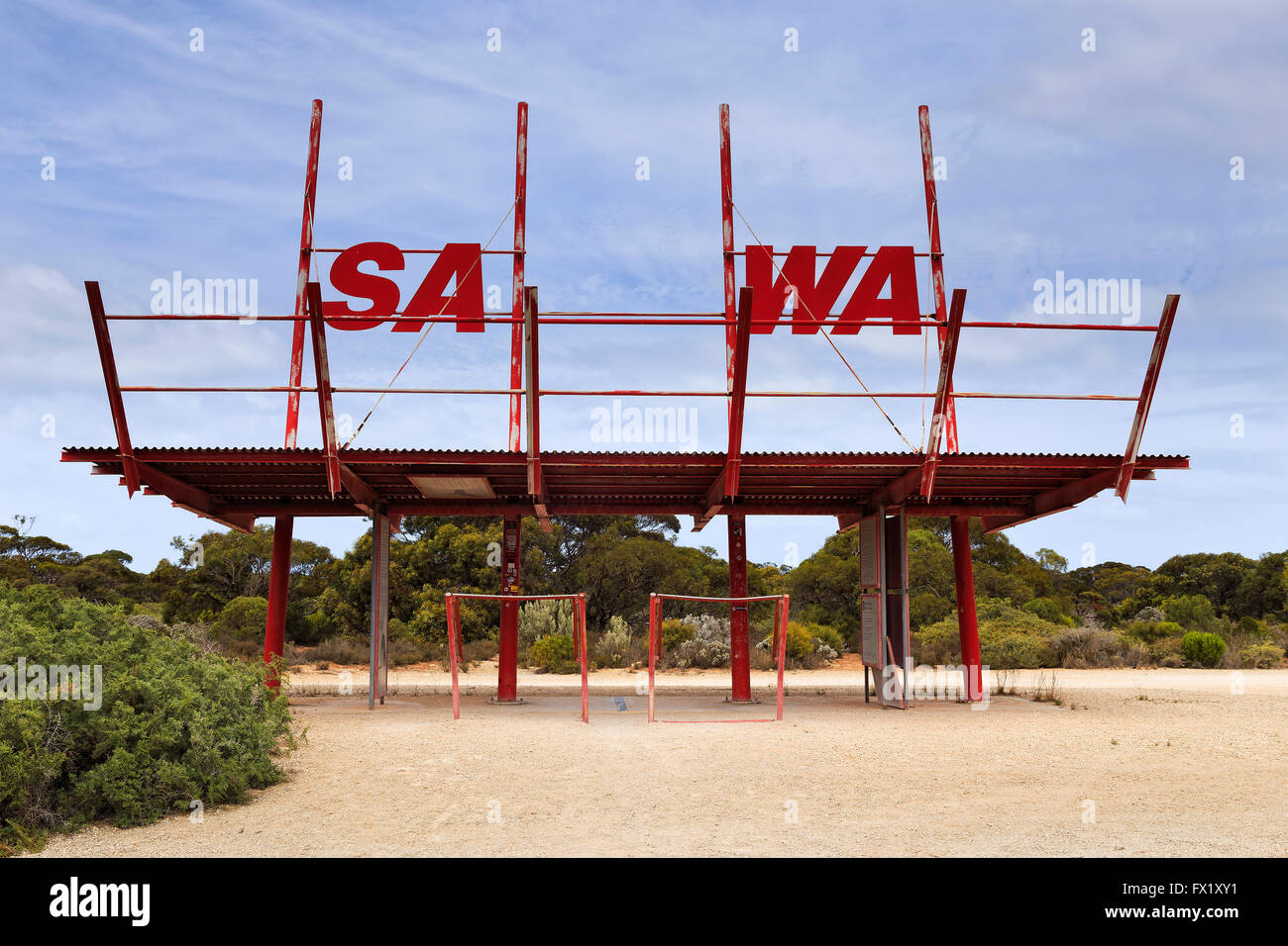 SA WA border village and border sign in a shape of old metal gate pavilion against blue sky in remote outback. - Stock Image