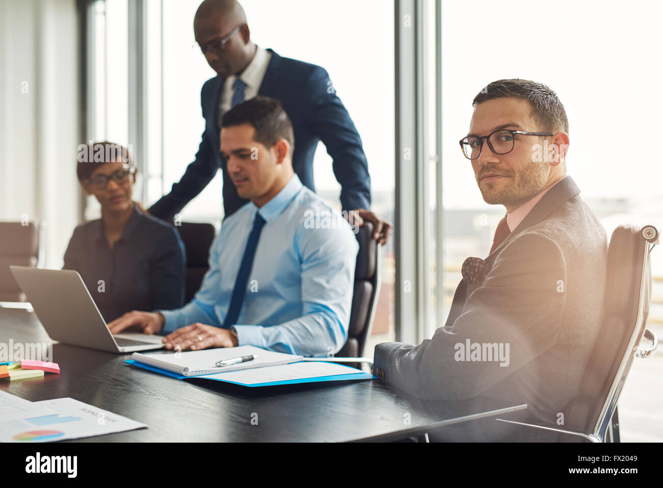 Professional young multiracial business team seated working around a table in the office with a young man in the - Stock Image