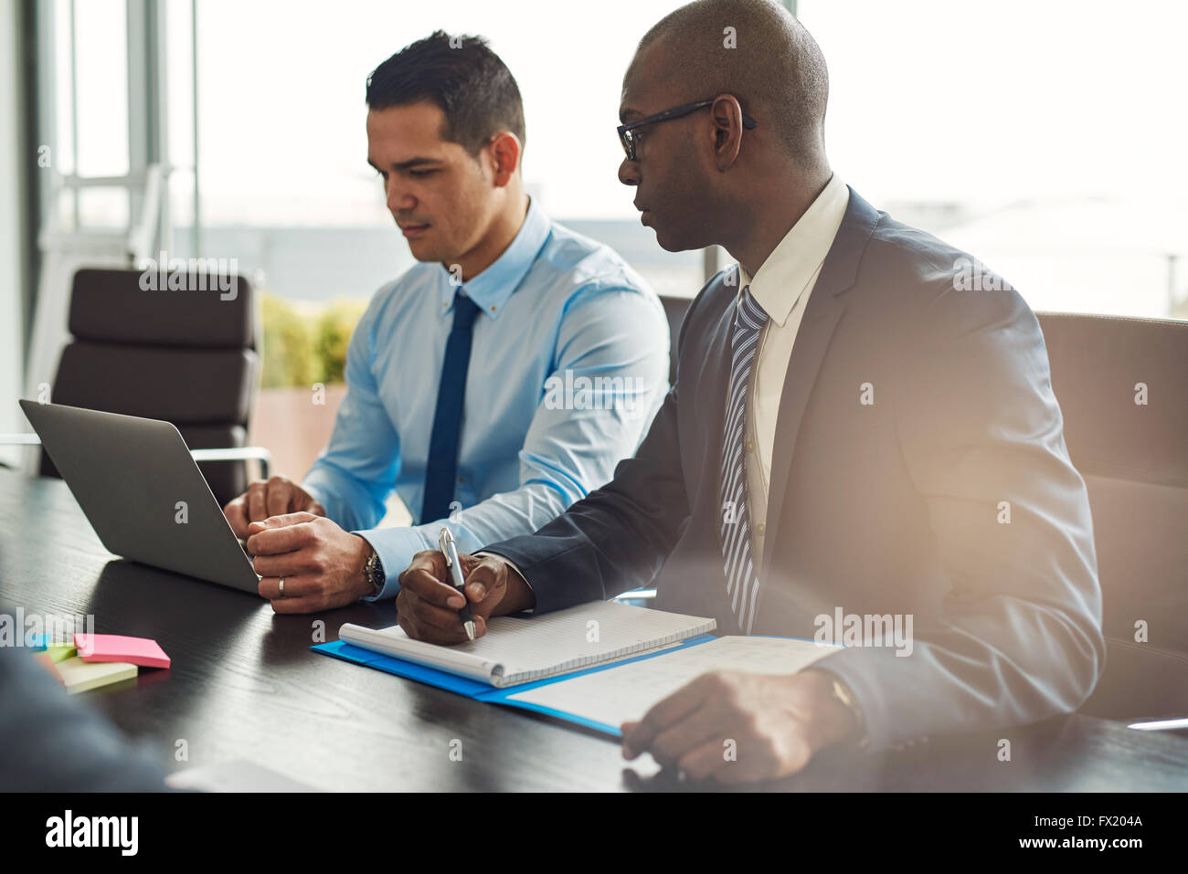 Two experienced business executives in a meeting seated at a table discussing paperwork and information on a laptop - Stock Image